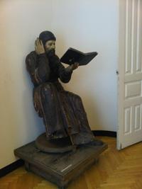 Экспозиция краеведческого музея. Деревянная скульптура Читающий монах